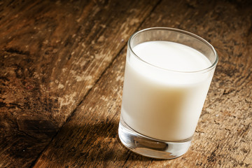 A glass of fresh milk on old wooden table, selective focus
