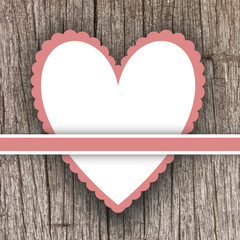 Scalloped pink heart frame on wooden wall