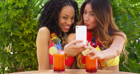 Two best friends taking selfie while on tropical vacation