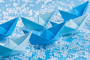 Fleet of blue Origami paper ships on blue waterlike background
