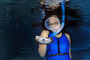 Female snorkeler underwater with sea shell