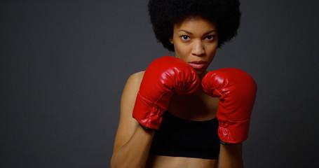 Black woman boxer punching towards camera