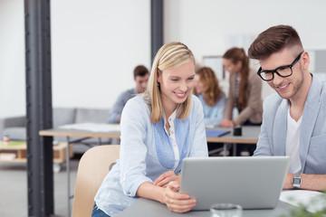 kollegen arbeiten zusammen am laptop