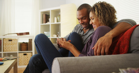 Black couple using smartphone together on couch