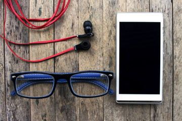 cellphone and glasses and earphone on wooden background, listening set