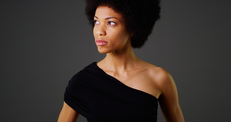 African woman in stylish black dress on grey background