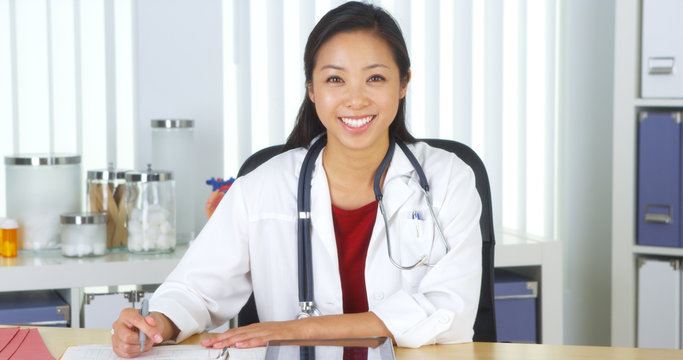Asian doctor talking to camera at desk
