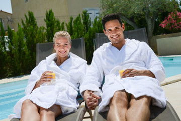 beautiful young couple resting in deck chairs with bathrobe by the pool of a thalasso resort