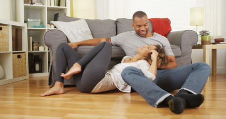 Black couple sitting on floor talking