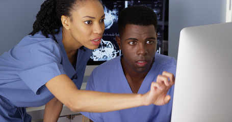Female medical specialist working with colleague on computer