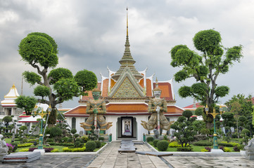 Grounds of Wat Arun in Bankgkok Thailand feature distinctive temple architecture with guardian figures and and decorative gardening