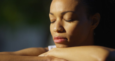 Black woman sitting with eyes closed outdoors