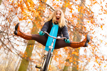 girl relaxing in autumnal park with bicycle
