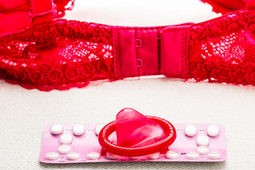Pills and condom with lace lingerie.
