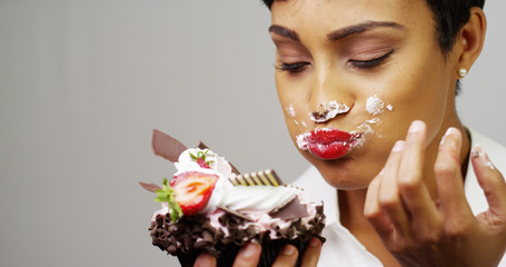 Black woman making a mess eating a huge fancy dessert