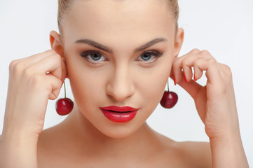 Attractive young girl with red appetite cherry