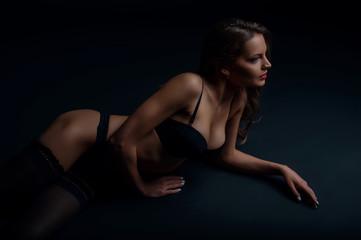 Attractive young girl is relaxing in dark underwear