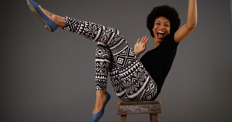 Happy black woman dancing on chair