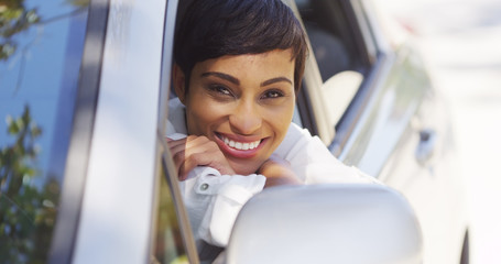 African woman smiling and looking out of car window