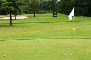 White flag on a golf course, focus on the flag