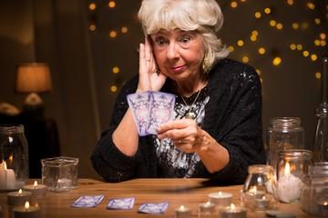 Shocked fortune teller reading cards