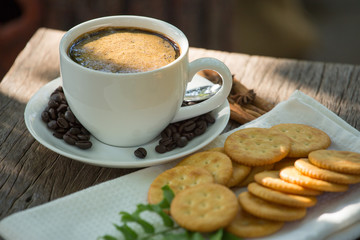 Cup of coffee on a wooden board and biscuits