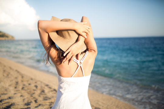Summer beach fashion woman enjoying summer and sun,walking the beach near clear blue sea,putting her hands behind her beck.Concept of summer feeling,freedom,pensive emotional portrait