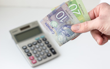 horizontal image of a hand holding a 20 and a 10 dollar canadian bill with  calculator blurred on white background