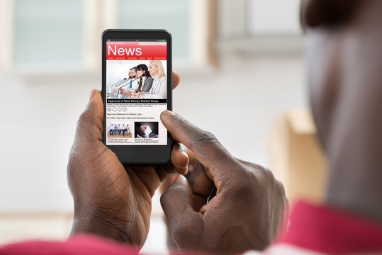 African Man Reading News On Cellphone