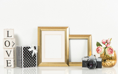 Golden picture frame, rose flowers and vintage camera. Retro sty
