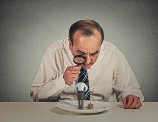 boss skeptically looking at employee through magnifying glass