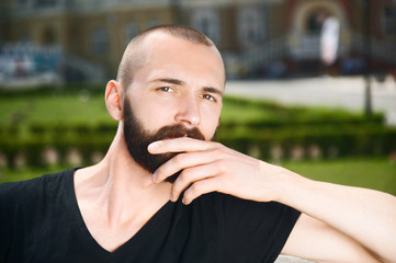 Attractive young hipster guy is having rest outdoors