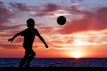 Silhouette of a boy playing football or soccer at the beach with
