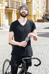 Attractive young hipster guy is cycling in city