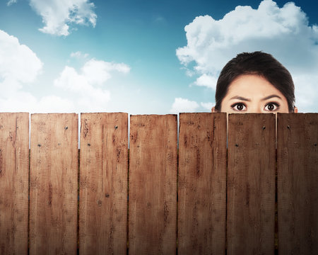 A woman head behind wooden fence