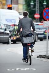Fototapete - Male bicyclist on the street, with headphones