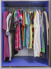 Wardrobe with hanging clothes on hangers