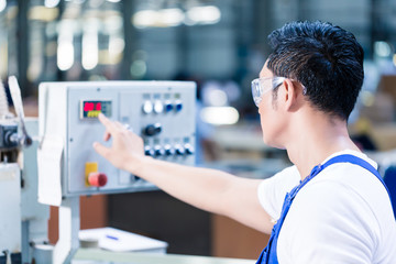 Worker pressing buttons on CNC machine in factory