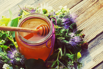 Honey in a glass jar the tied gift tape with a bow with June flowers melliferous herbson a wooden surface. Honey with flowers