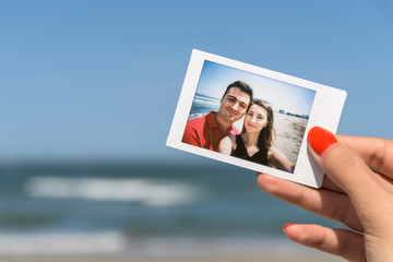Girl Holding Instant Photo Of Young Happy Couple