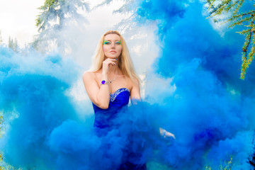 Beautiful young woman in a cloud of a bright blue smoke