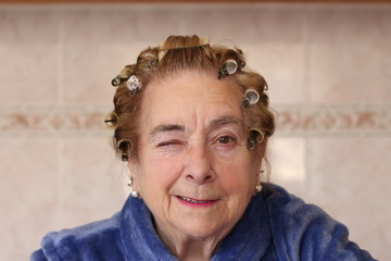 Winkey housewife in hair curlers wearing blue robe