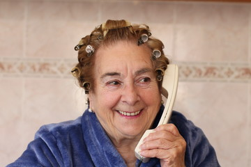 Funny housewife in hair curlers wearing blue robe