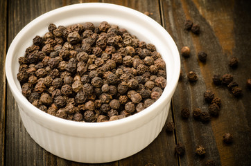 Black pepper in the white bowl on wooden background