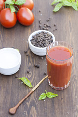 Tomato juice in glass with basil, spices and tomatoes cherry, selective focus