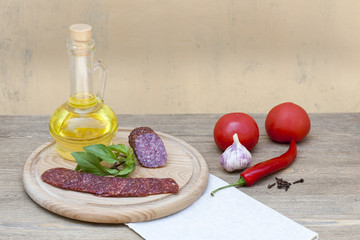 Salami sausage and sunflower oil in the bottles with herbs, tomatoes and spices on wooden table, selective focus
