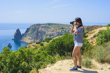 young caucasian female with camera on a cliff, woman taking photos on seaside