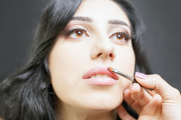 Specialist in beauty salon gets lipstick, lip gloss, professional make-up.