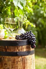Wall Mural - wine on wooden barrel on green garden terrace