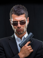 man in suit with handgun
